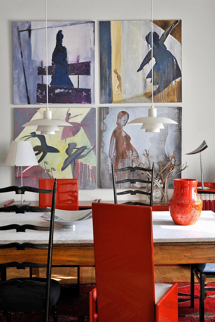 Holztisch mit Marmorplatte, schwarze und rote Stühle im Essbereich, Kunstwerke an der Wand