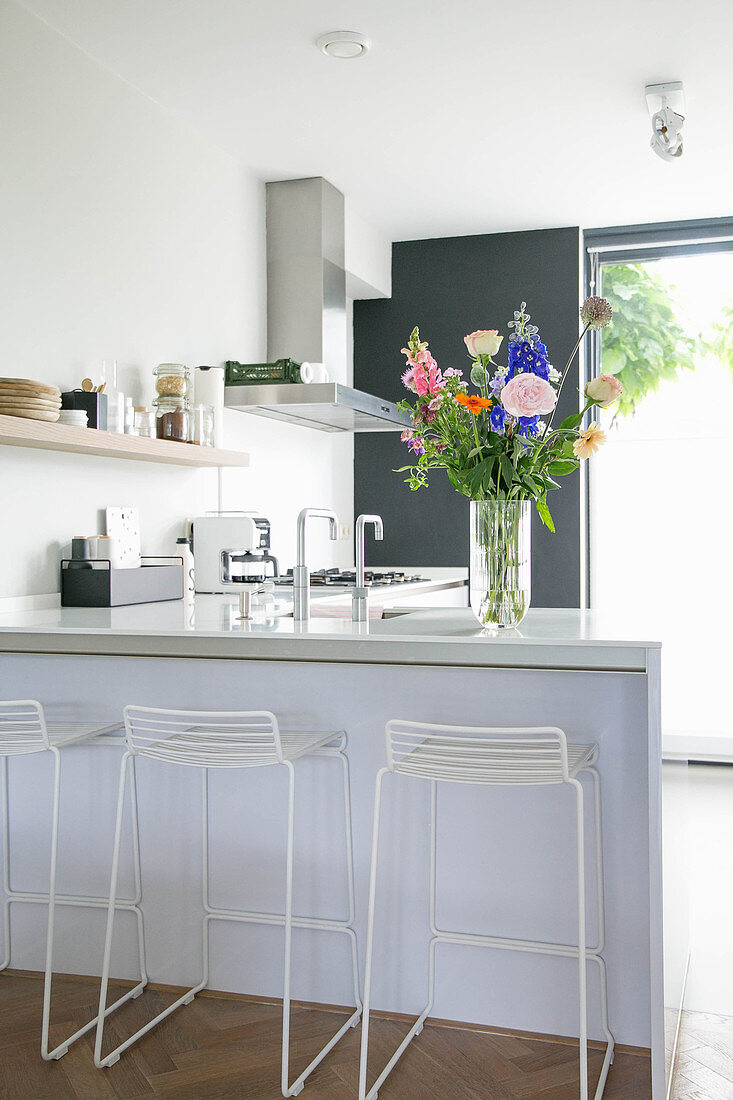 Vase of colourful flower on counter with bar stools in kitchen