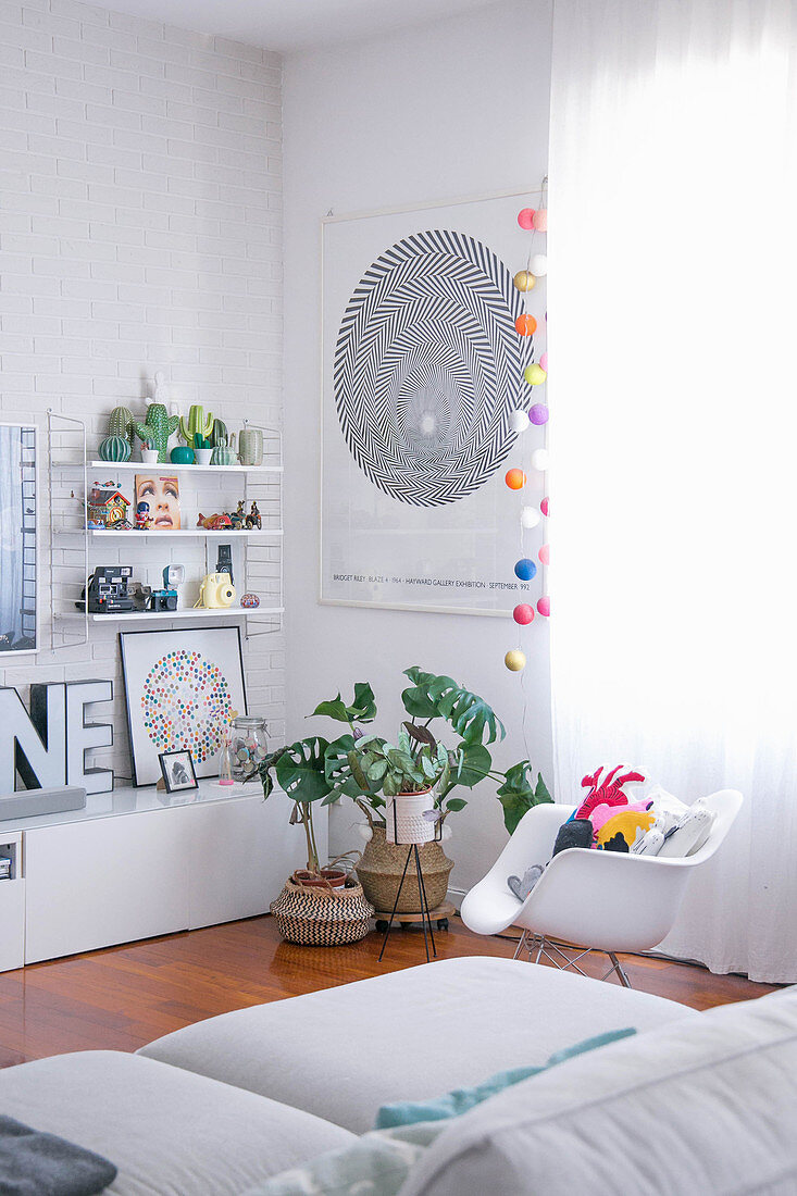 Shell chair, houseplants and low sideboard in white living room