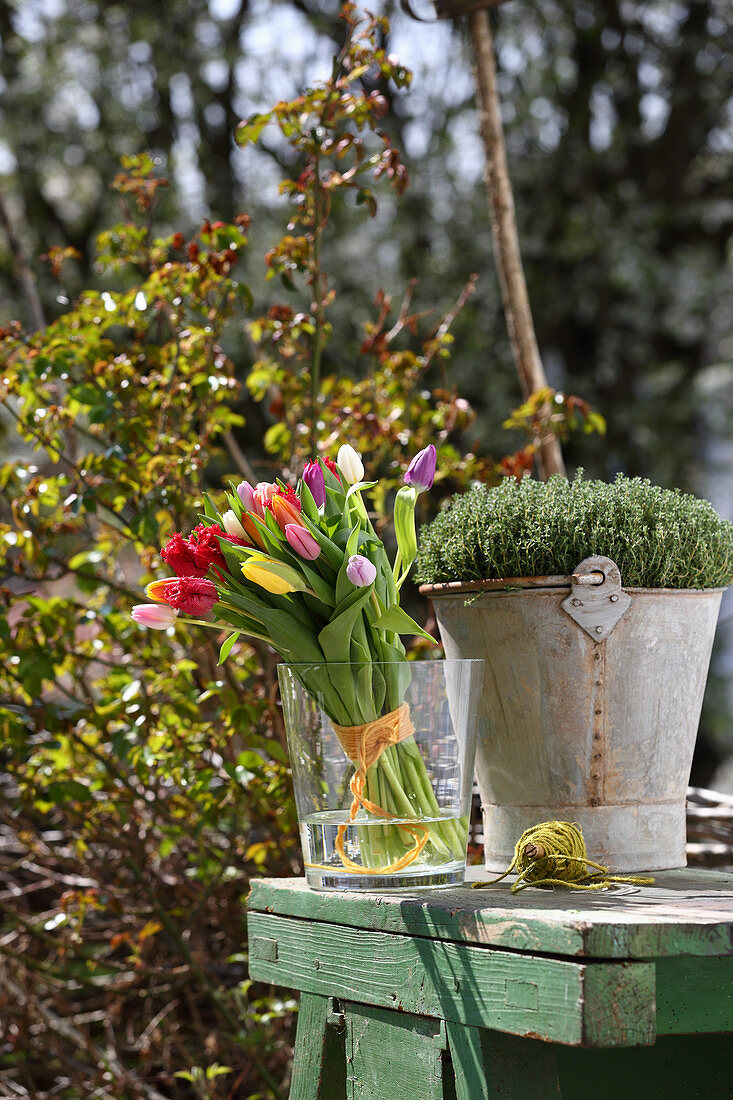 Colourful bouquet of tulips in glass vase on garden