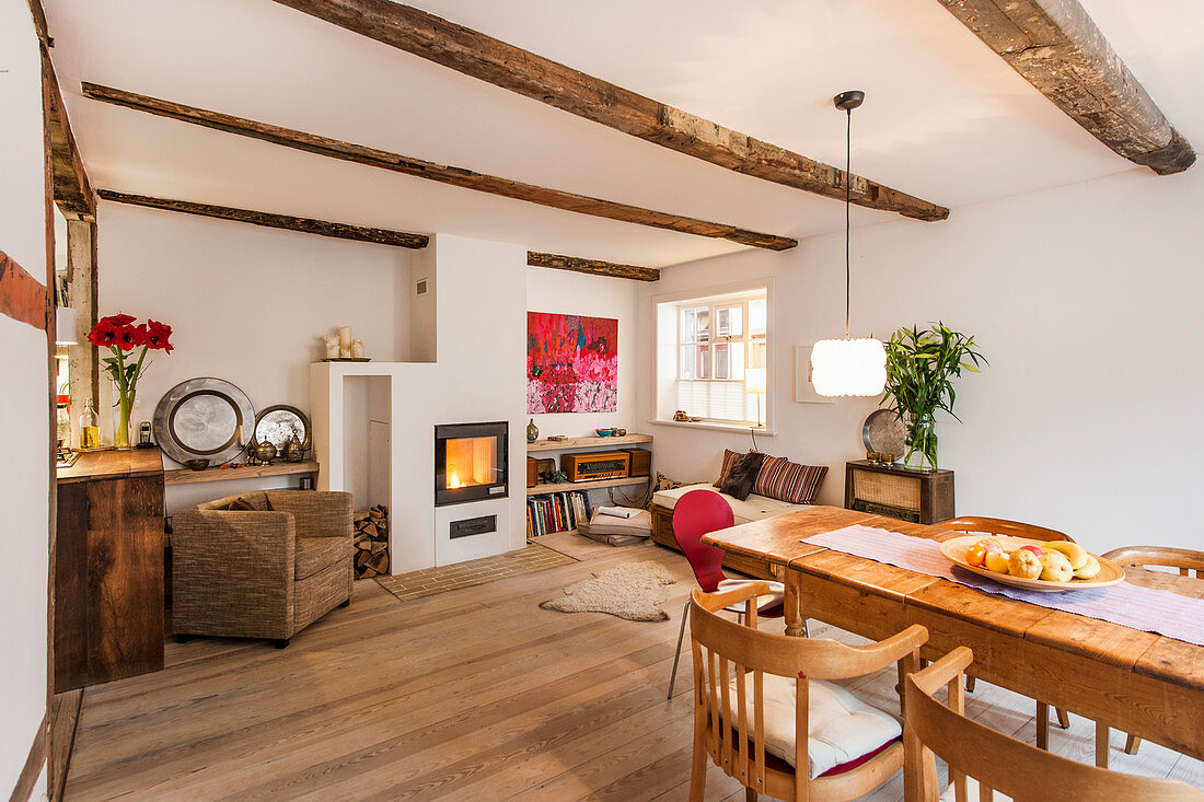Rustic dining table, seating area and fireplace in open-plan interior