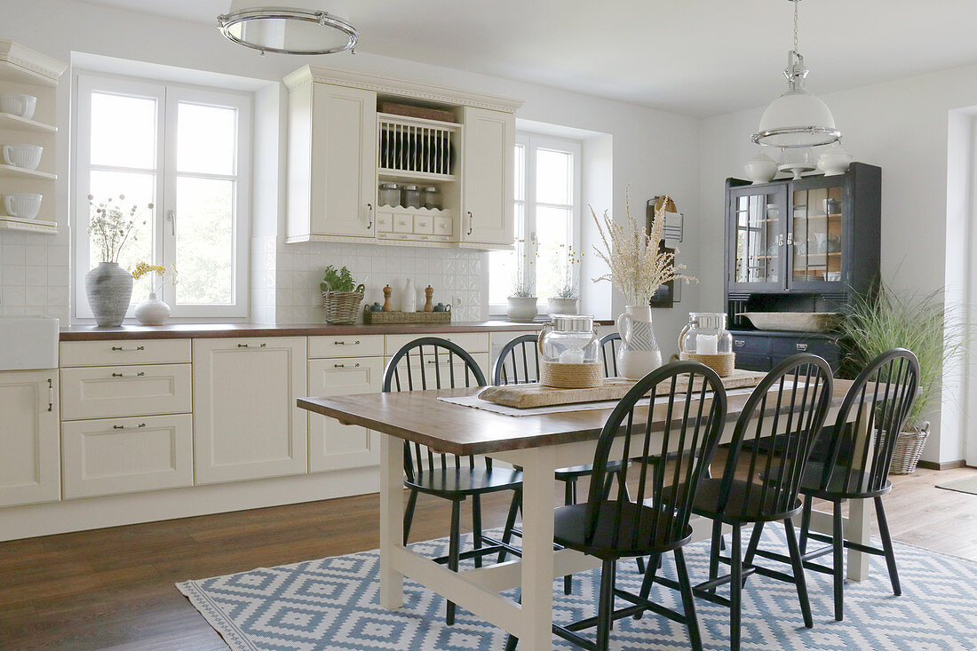 Dining table and dark chairs on rug in country-house kitchen