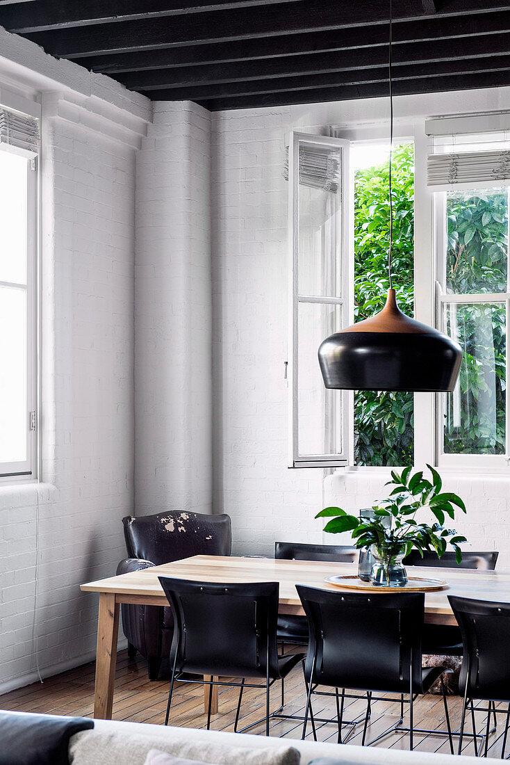 Schwarze Stühle am Esstisch im Altbau mit weißen Backsteinwänden
