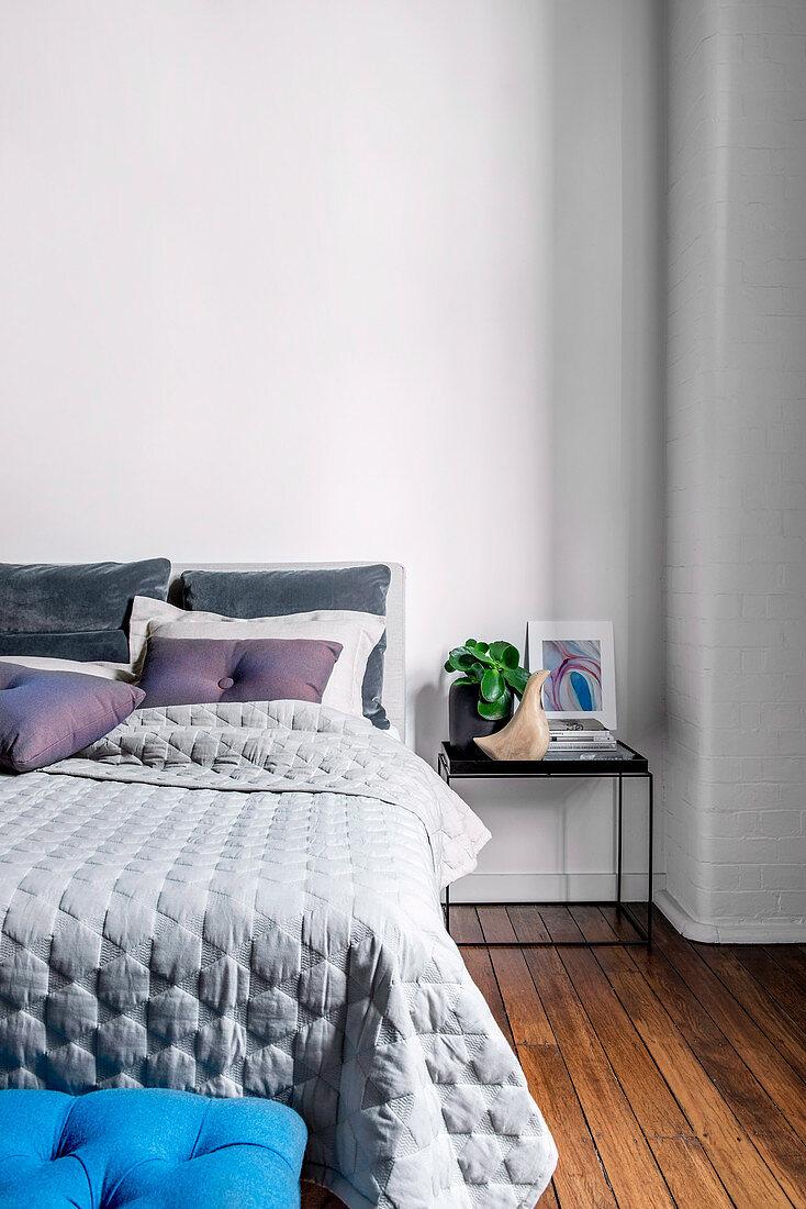 Nachttisch neben dem Bett im Schlafzimmer mit Holzboden