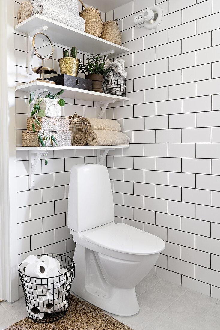 Shelves holding bathroom utensils over toilet in corner of bathroom