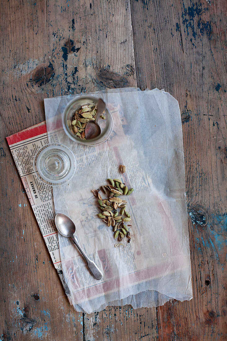 Cardamom on translucent baking parchment and newspaper