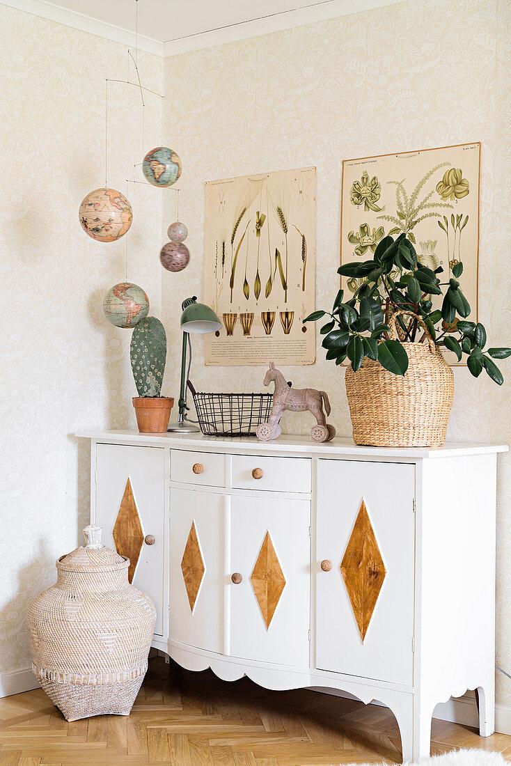 Houseplants on sideboard, mobile of planets and botanical drawings