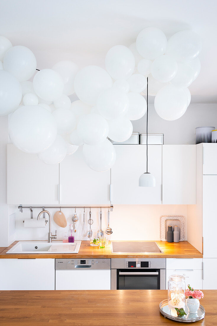 Cloud of white balloons above kitchen island