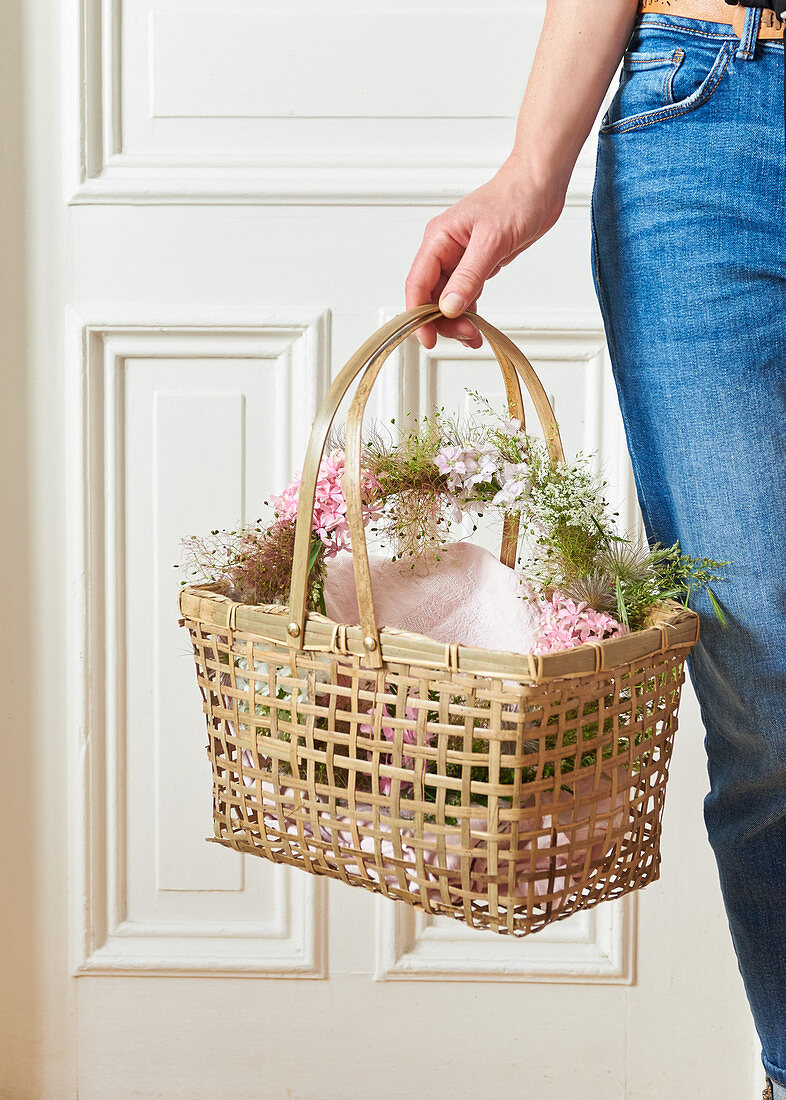 Wreath of flowers and seed heads in basket held in hand