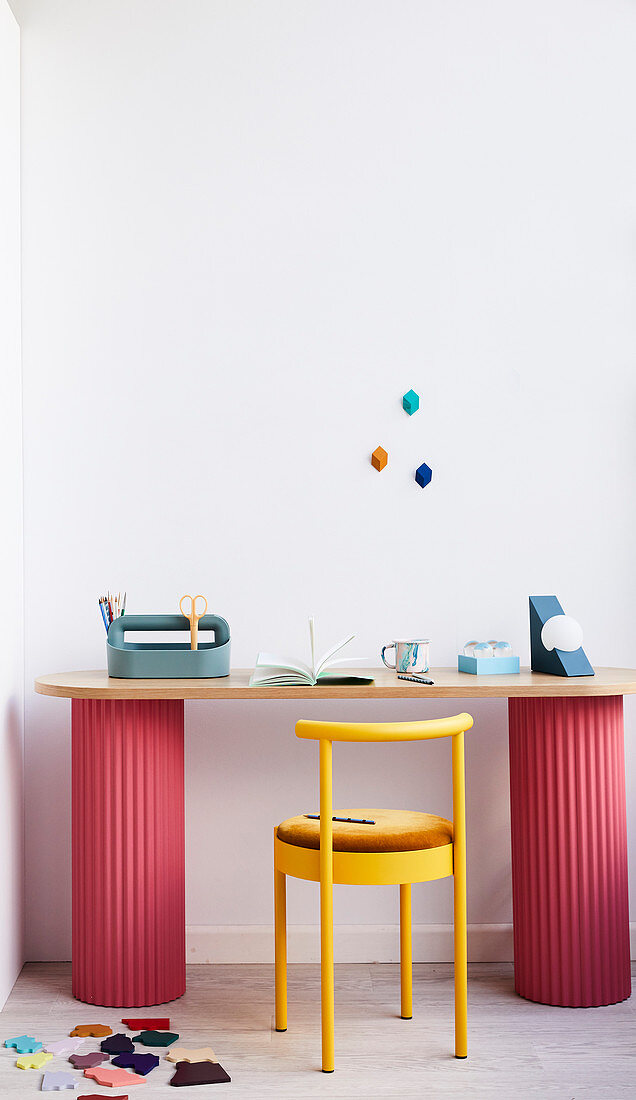 Gelber Stuhl am Schreibtisch auf zwei roten Säulen