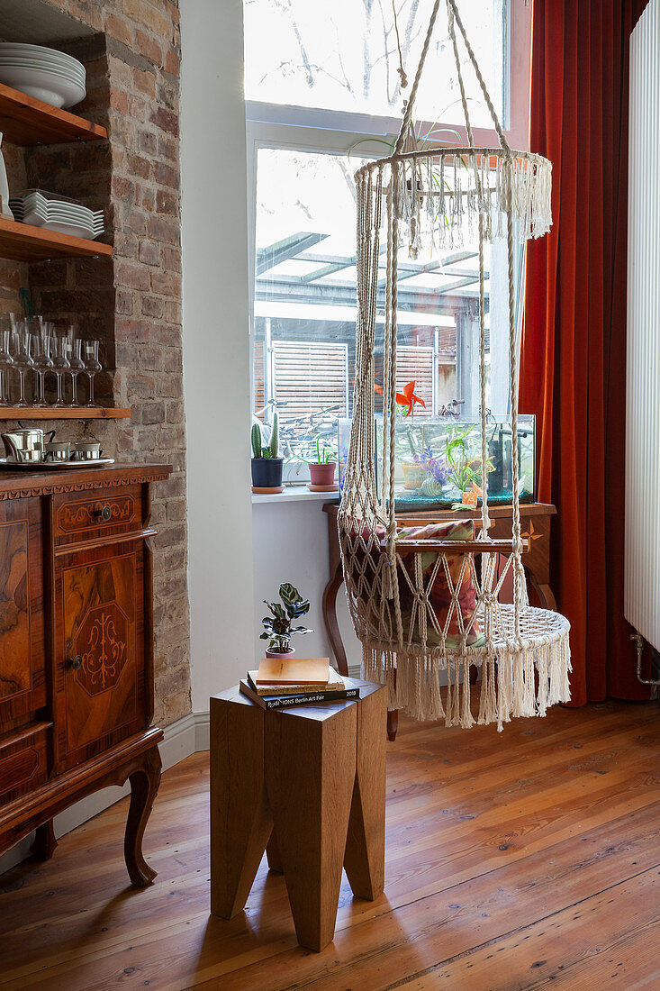 Macrame hanging chair and wooden stool in front of window