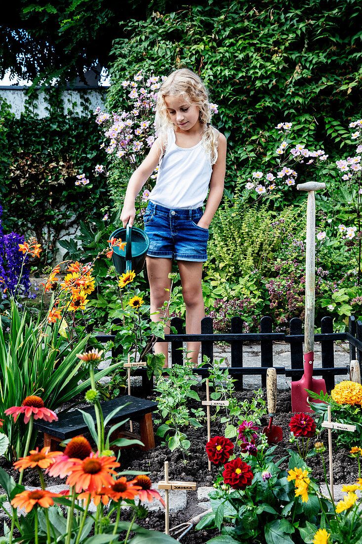 Girl watering flowers in the fenced mini-garden