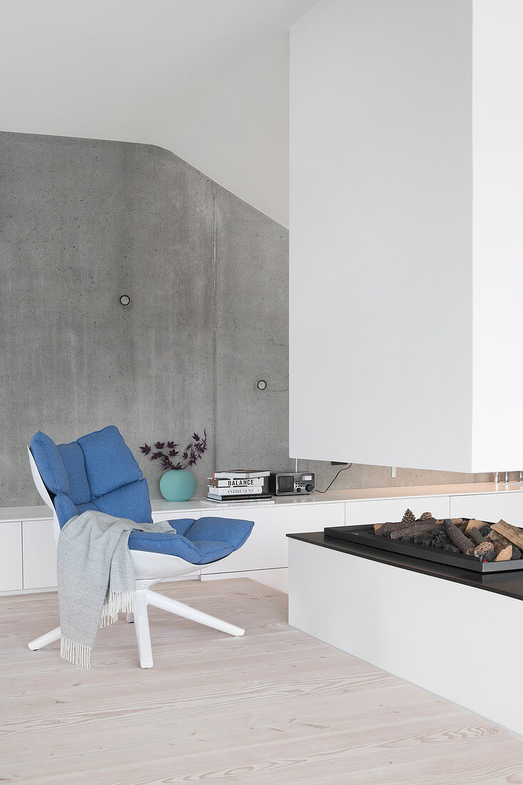 Easy chair next to open fireplace in front of concrete wall in architect-designed house