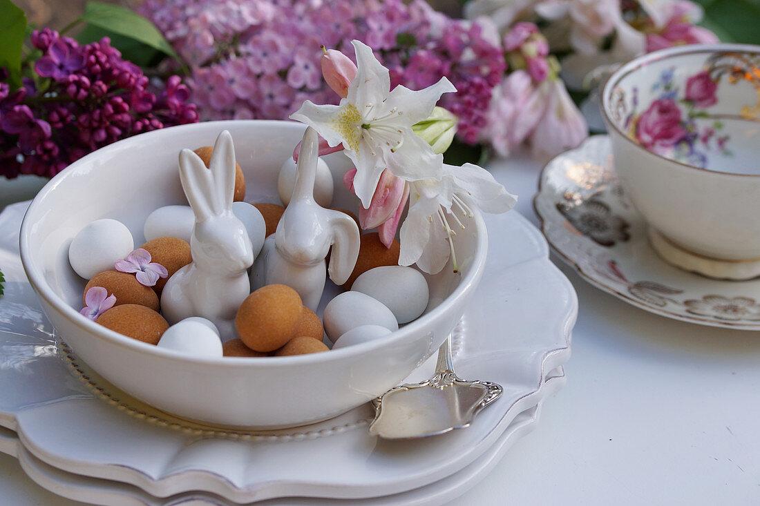 Porcelain Easter bunnies between marzipan eggs in bowl