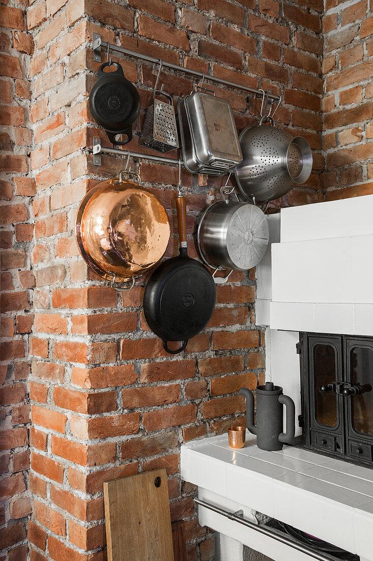 Kitchen utensils hung on brick wall in white kitchen