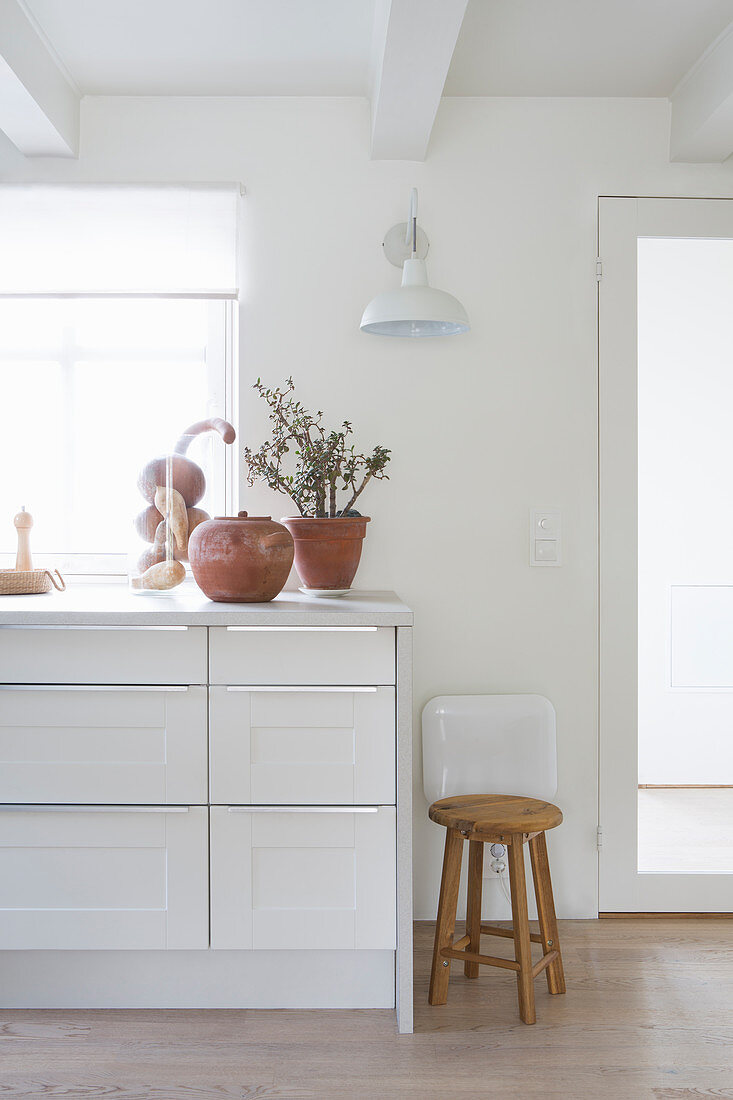 Terracotta pots on white kitchen counter and wooden stool