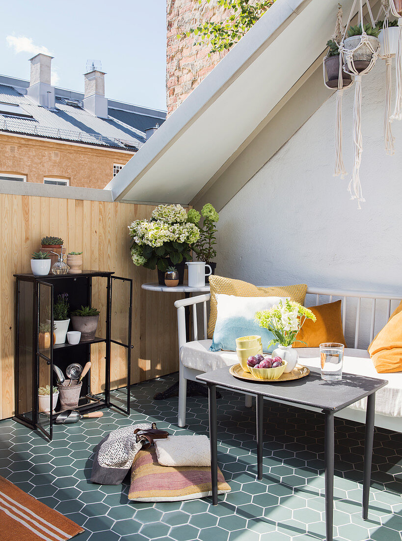 Sunny seating area on inverted dormer roof terrace with honeycomb tiles, bench and table