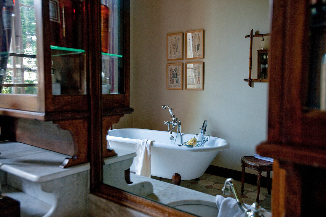 Wooden cabinets and free-standing bathtub in antique-style bathroom