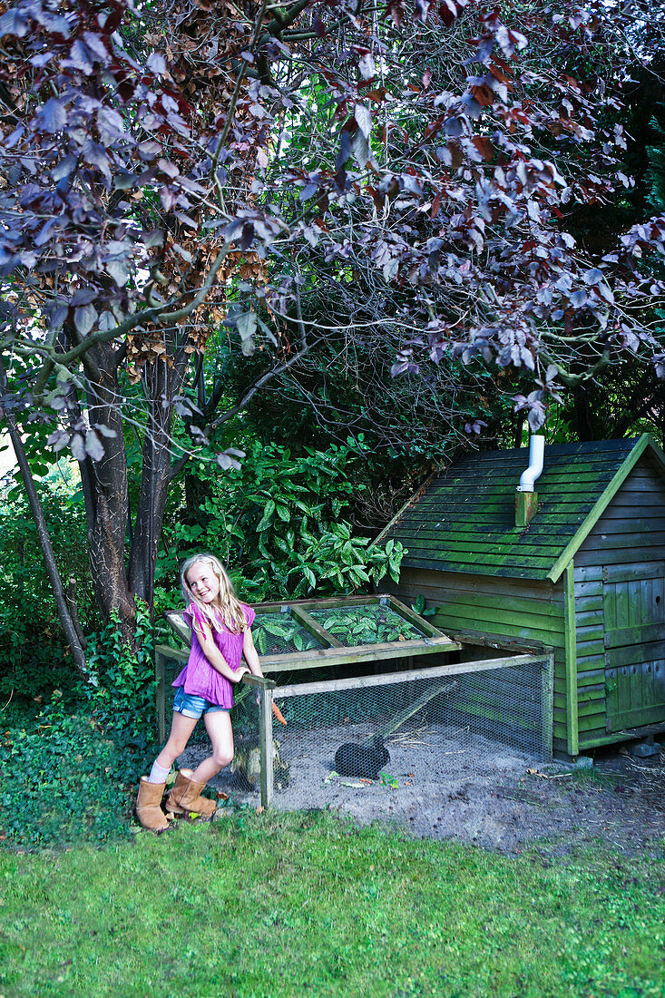 Little girl next to rabbit run in garden