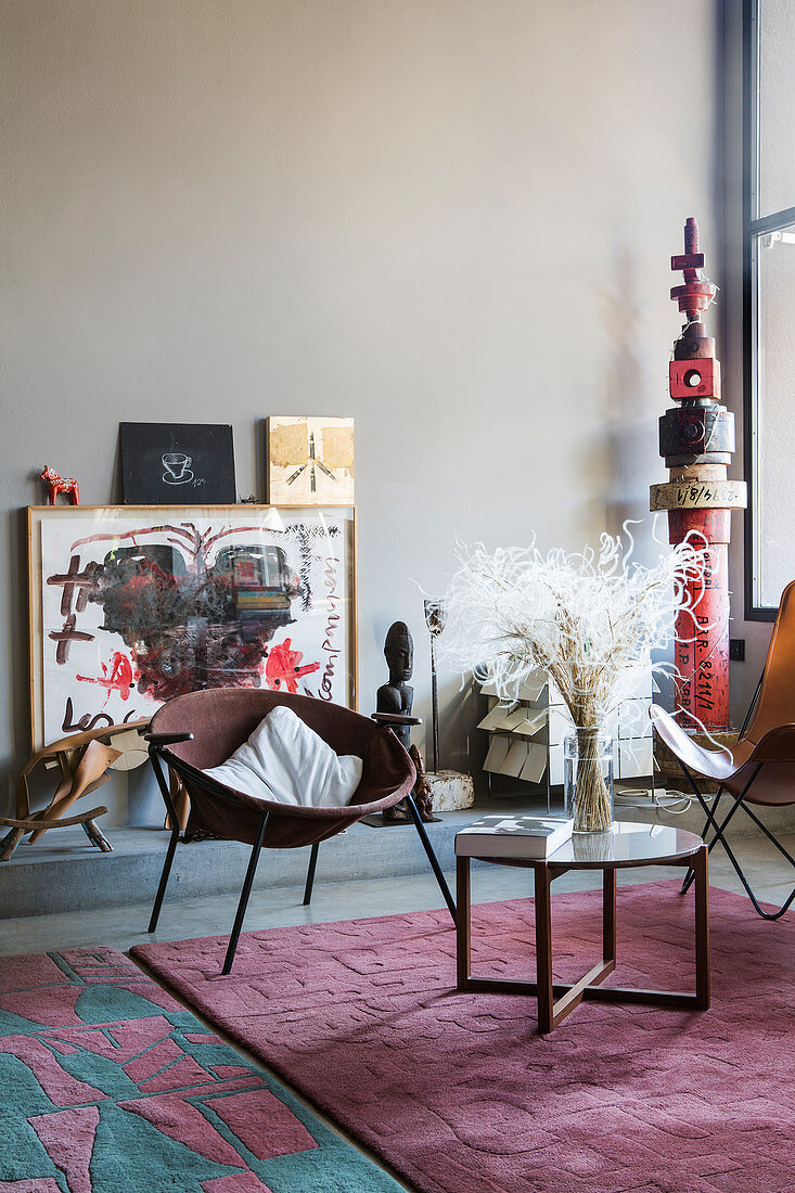 Side table and easy chairs on pink rug in front of various artworks