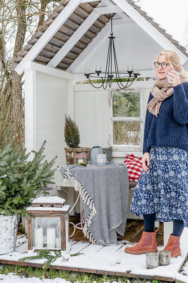 Woman standing on deck of cosily decorated arbour in wintry garden