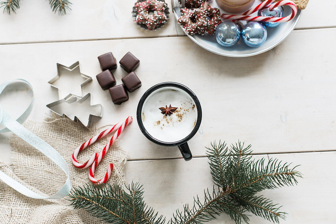 Hot drink in enamel mug, biscuits and fir branch