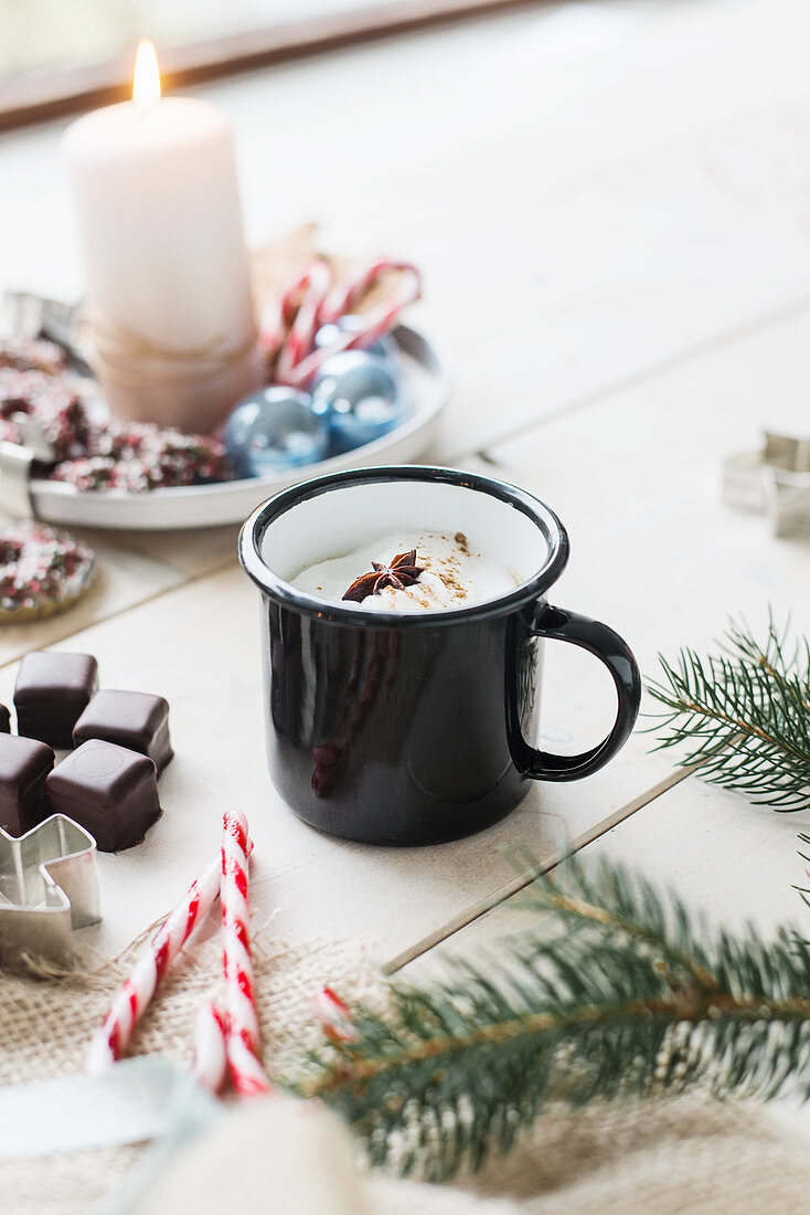 Hot drink in enamel mug, sweets and fir branch