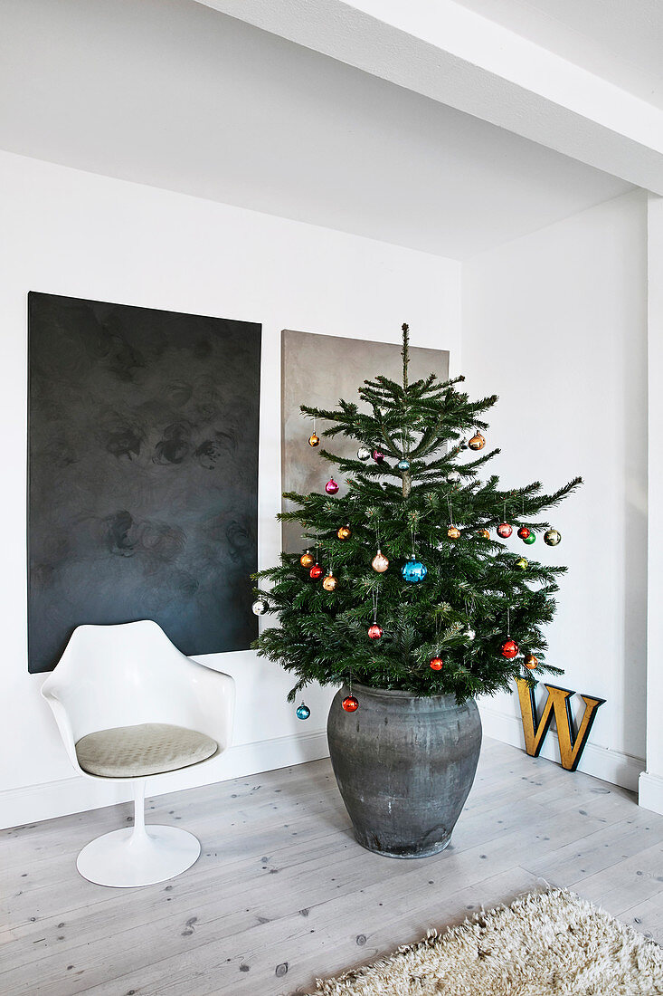 Decorated Christmas tree and Tulip chair in front of abstract paintings on wall