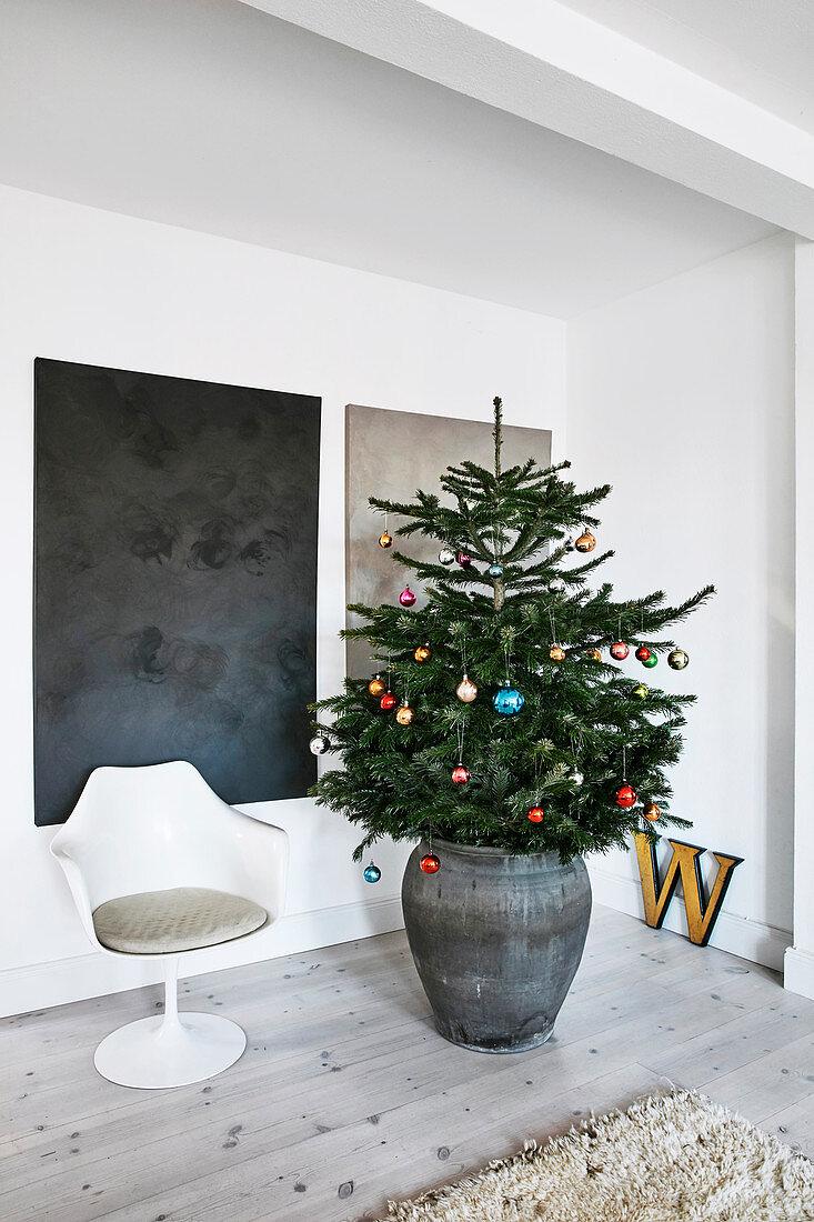 Geschmückter Tannenbaum vor abstrakten Wandgemälden neben Tulip-Stuhl