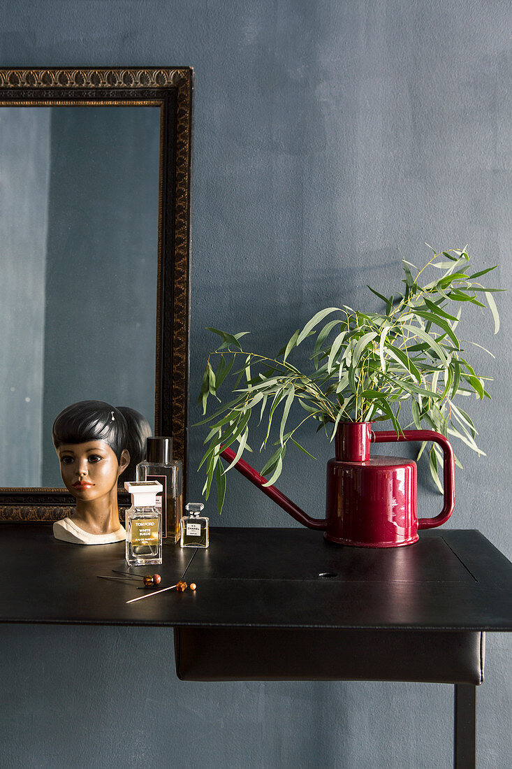 Red watering can used as vase and retro bust on dressing table