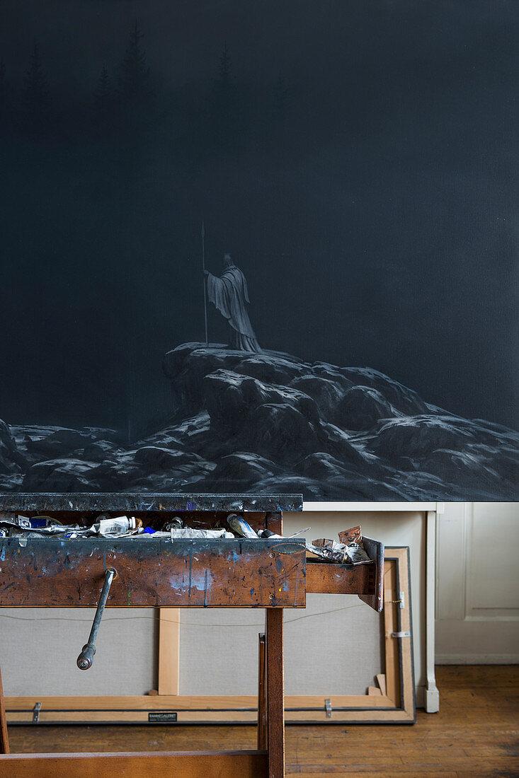 Dark painting on easel in artist's studio