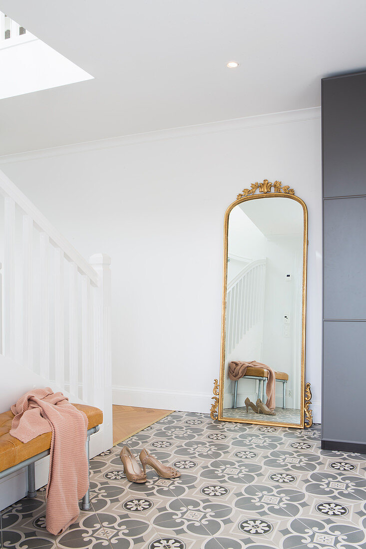 Antique full-length mirror in foyer with patterned floor