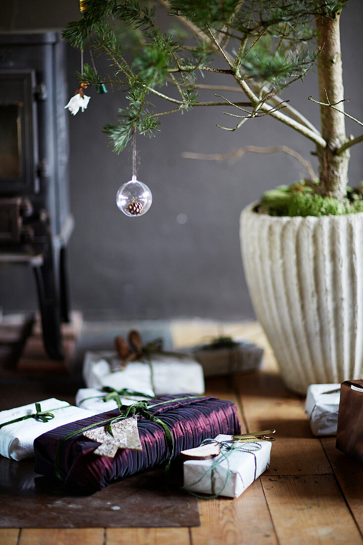 Wrapped Christmas presents below small tree