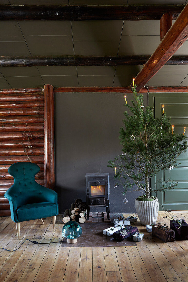 Decorated Christmas tree, gifts and armchair in front of wood-burning stove