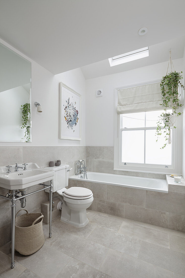 Vintage-style washstand, toilet and fitted bathtub below skylight in bright bathroom