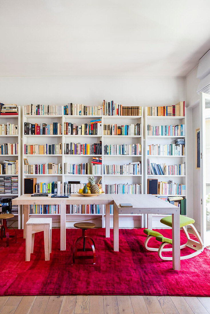Two three-legged tables arranged in an L on hot-pink rug in front of bookcase