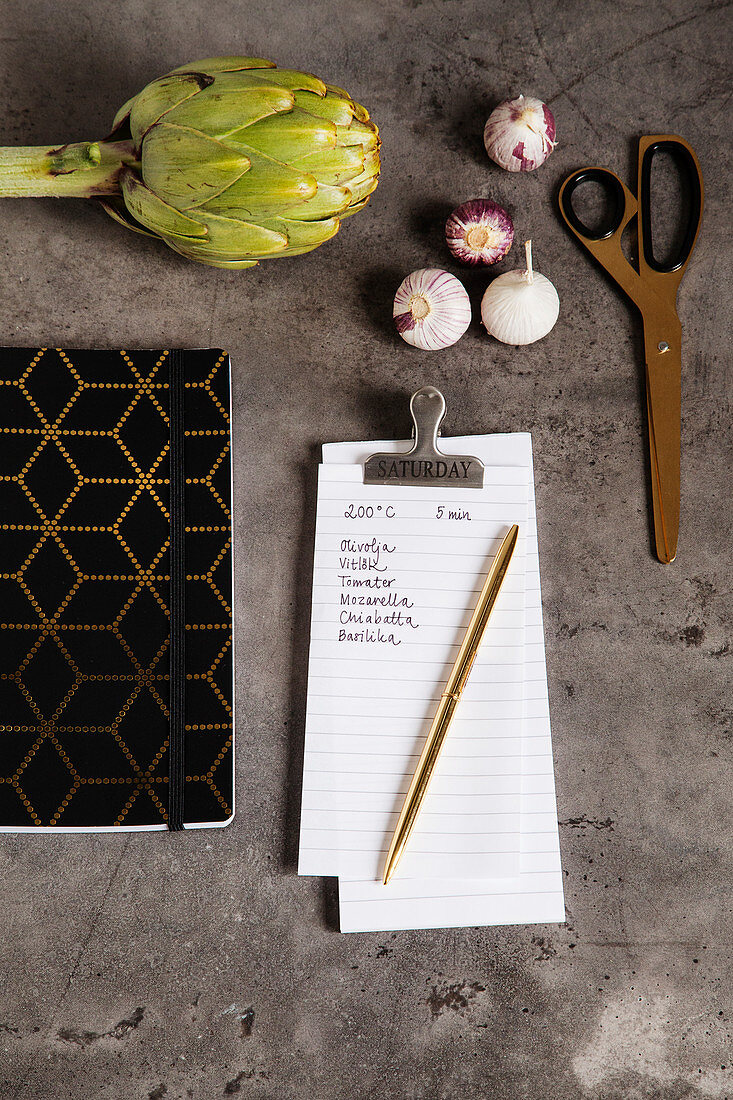 Vegetables, scissors, notebook and shopping list on kitchen worktop