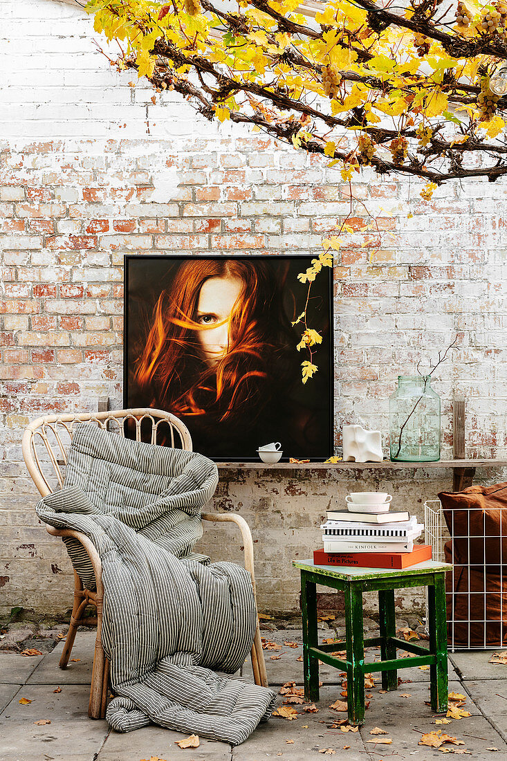 Seating area with photograph on brick wall below autumnal vines