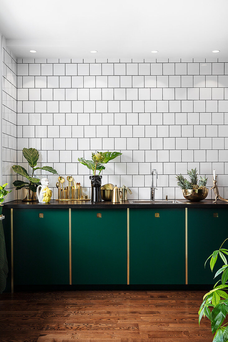 Dark green cupboards and exotic accessories in kitchen