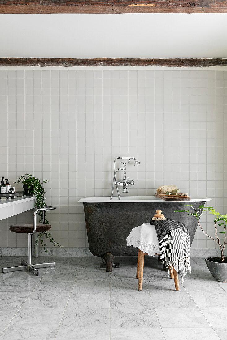 Kleine freistehende Badewanne im schlichten Bad in Grau und Weiß