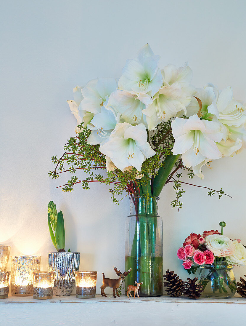 Festive arrangement of vase of white amaryllis and tealights on ledge