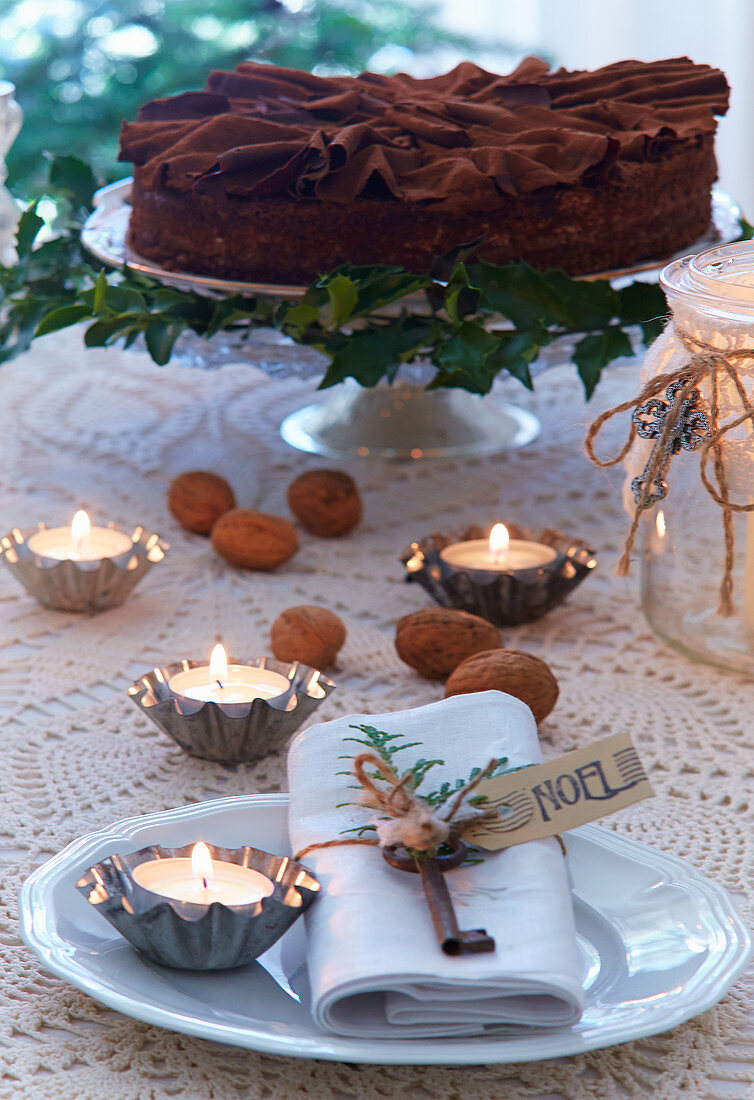 Schokoladentorte auf weihnachtlich gedecktem Tisch mit Teelichtern in Backförmchen