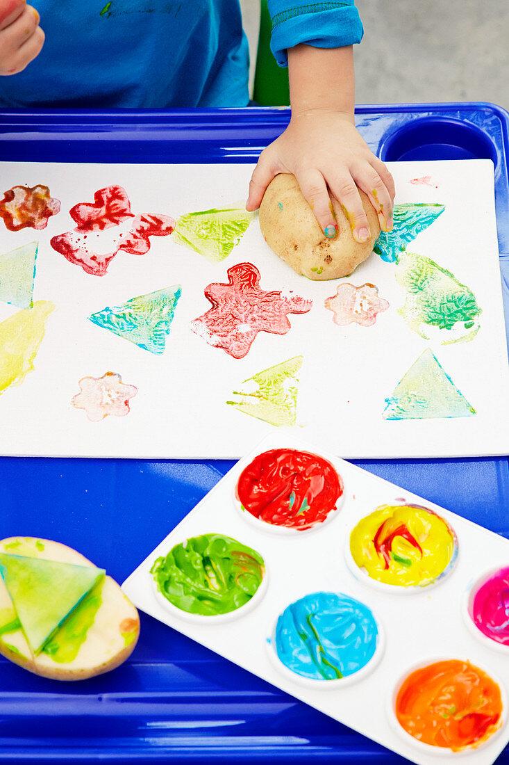 Child making colourful potato prints