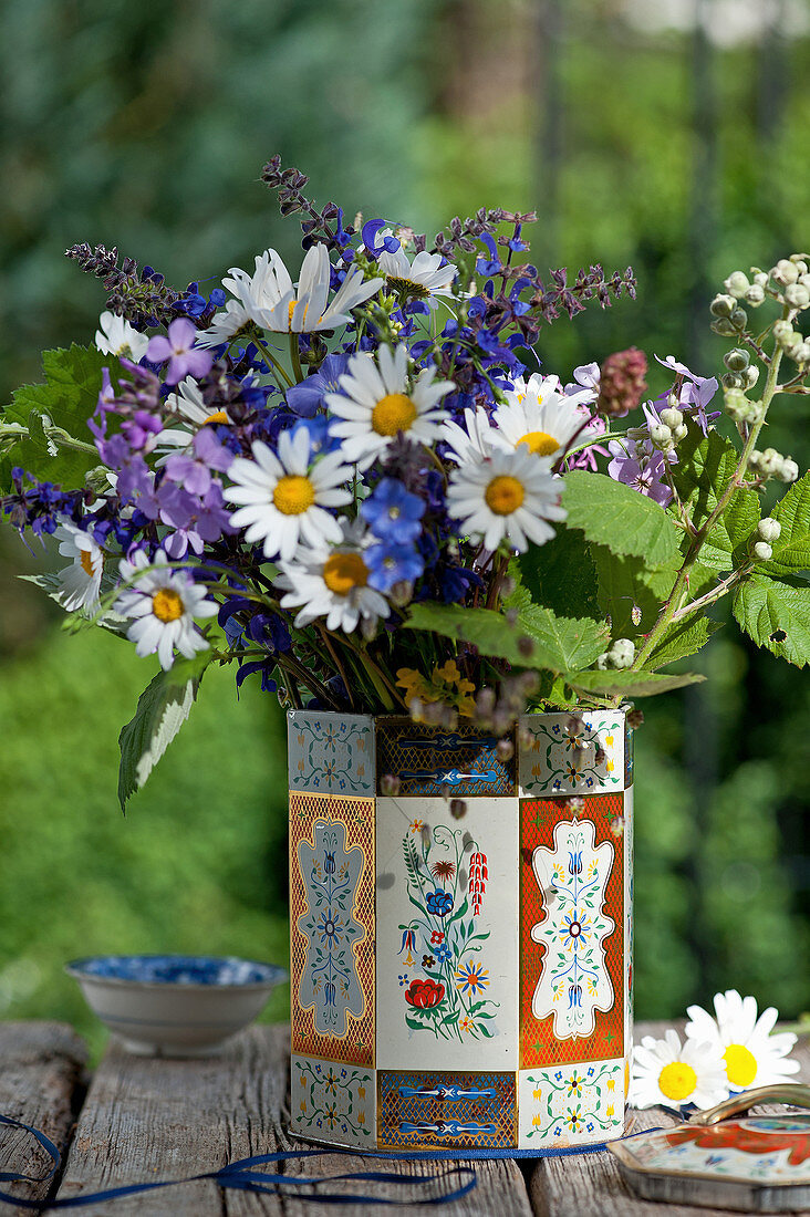 Bouquet of wildflowers with ox-eye daisies, meadow sage, honesty flowers and blackberry sprig in tea caddy