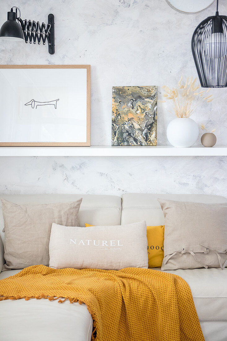 Picture painted with marble pour technique on shelf above sofa with beige and ochre cushions