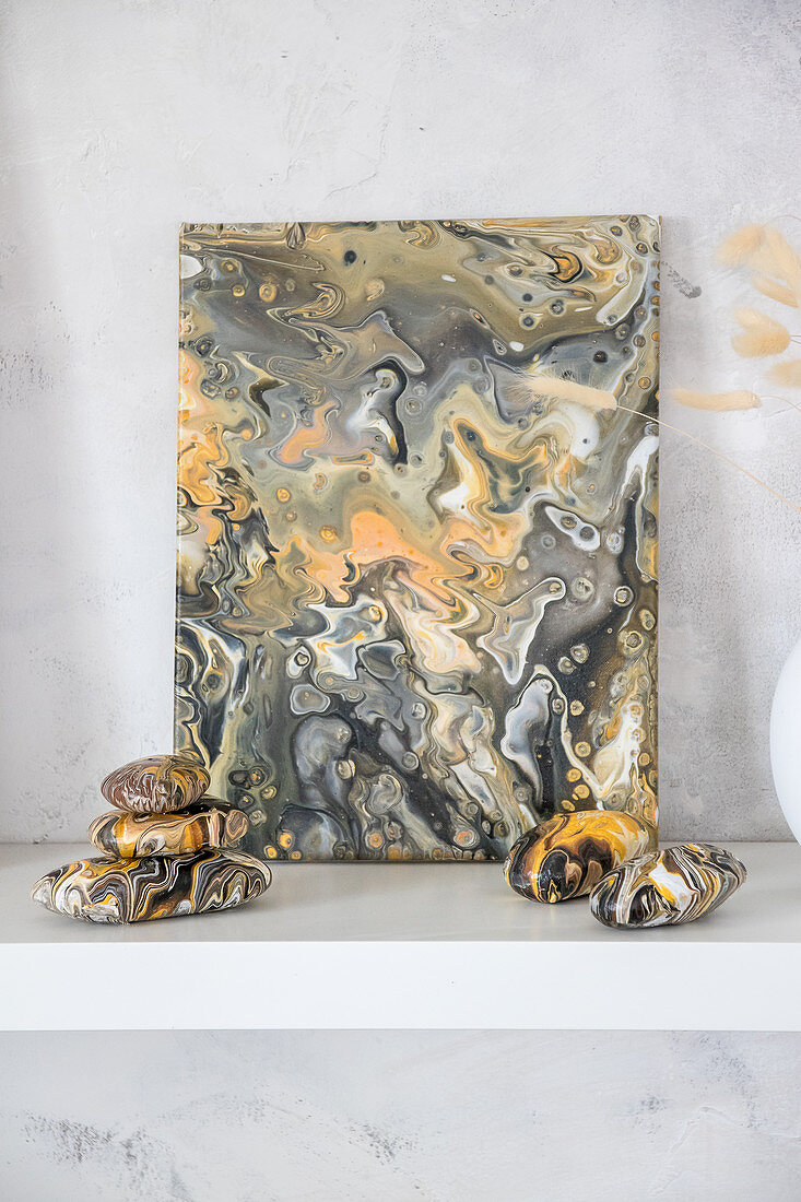 Canvas and pebbles painted with marble pour technique in natural colours