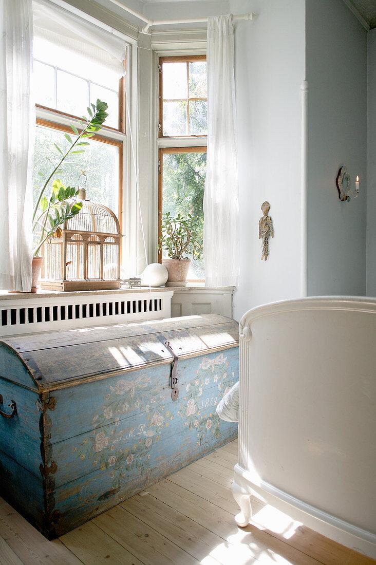 Old blue trunk below bay window in sunny bedroom