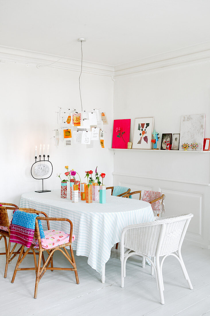 Wicker chairs around table in white dining room with brightly coloured accents