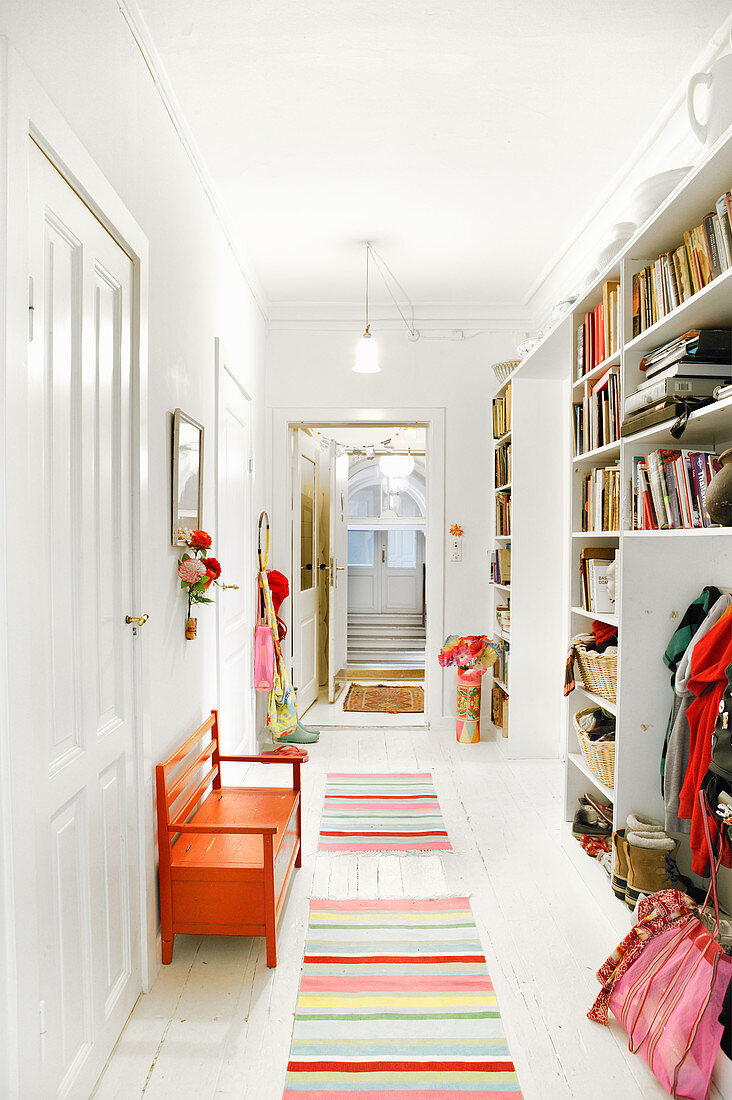 Striped, multi-coloured runners and orange bench in white hallway