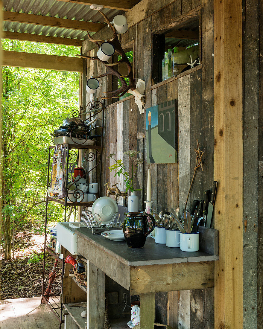 Outdoor kitchen on roofed terrace of small wooden shed